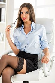 stock photo of short legs  - A young attractive woman in a short skirt sits cross-legged in office armchair holding glasses and smiling looking at the camera. ** Note: Shallow depth of field - JPG