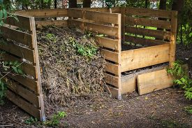stock photo of decomposition  - Wooden compost boxes with composted soil and yard waste for garden composting in backyard - JPG
