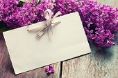 stock photo of life event  - Postcard with fresh splendid lilac flowers and empty tag for your text on aged wooden background - JPG