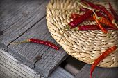 pic of chili peppers  - Red hot chili peppers on an old wooden table texture - JPG
