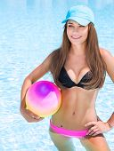 foto of sportive  - Sexy sportive girl having fun in swimming pool  with ball - JPG