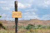 stock photo of barbed wire fence  - pillar with a prohibition sign and barbed wire fence - JPG
