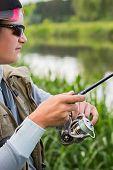 image of fishermen  - Fisherman on the river bank in sunglasses - JPG