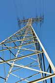 stock photo of voltage  - Industrial high voltage electrical tower with cables against blue sky - JPG