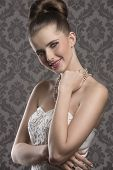 foto of aristocrat  - elegant fashion portrait of smiling aristocratic woman with white decorated dress fine hairdo and precious pearls necklace - JPG