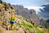 image of canary  - Young woman running or power hiking in mountains on sunny summer day - JPG