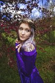 foto of crap  - Beautiful young woman in purple velvet medieval gown wearing a crown made of twigs in front of a crab apple tree - JPG