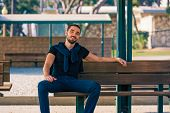 pic of sitting a bench  - Handsome smiling and casual young man sitting on bench - JPG