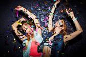 image of confetti  - Two energetic girls dancing in confetti falling - JPG