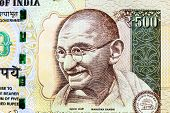 stock photo of indian  - Closeup macro view of Mahatma Gandhi on an Indian currency note - JPG