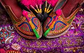 stock photo of shoes colorful  - Colorful ethnic shoes and camel decorations on violet Rajasthan cushion cover on flea market in India - JPG