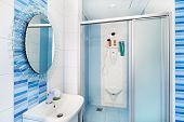 stock photo of shower-cubicle  - Modern blue bathroom interior with round mirror and shower cubicle - JPG