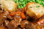 Casseroled beef stew with dumplings and peas