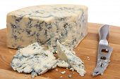 Stilton cheese on cheeseboard with knife.