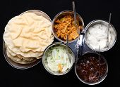 Indian poppadums with lime pickle, brinjal pickle, mint raita and onion salad.