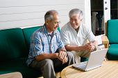 Two elderly men sitting with laptop