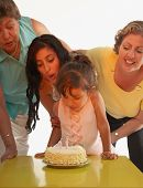 Young girl blowing out candles on her birthday cake