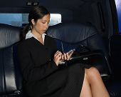 Businesswoman holding palm pilot in back seat of car