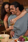 Couple hugging and drinking while cooking