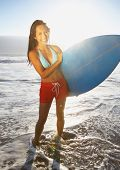 Full view portrait of woman holding surf board at beach