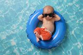 Newborn Baby Boy Floating On An Inflatable Swim Ring poster