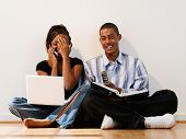 Young couple using cell phones and laptop