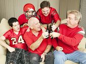 Superbowl football fans toasting success with their beer bottles.