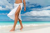 White pareo woman legs walking on tropical beach vacation. Closeup of barefoot female young adult lo poster