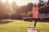 Senior woman in balancing yoga pose with morning sunflare poster