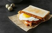Tasty toast with fried egg and bacon on table poster