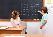 Schoolgirl Solving Math Equations At Chalkboard