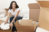 A beautiful single young woman unpacking boxes and moving into a new home.