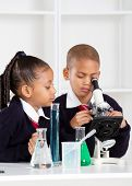 elementary school kids in science class using a microscope