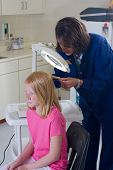 stock photo of lice  - Nurse checking for head lice on young patient - JPG