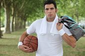 30 years old sportyman holding a basket ball and a sports bag