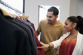 Young Hispanic couple looking at clothes in a clothes shop poster