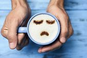 high-angle shot of a young caucasian man with a blue cup of cappuccino with a sad face drawn with co poster