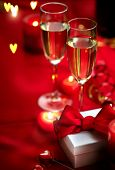 Valentines Day Romantic Dinner. Date. Table setting with Champagne in two glasses, candles and gift poster