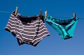 stock photo of boxer briefs  - Mens boxer shorts and saucy silk panties together on a suburban washing line in a gender concept - JPG