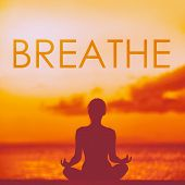 BREATHE yoga inspirational title on beautiful beach with woman meditating doing yoga at sunset. Word poster