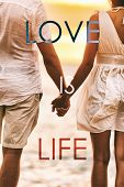 LOVE IS LIFE title written over couple in love holding hands at sunset beach honeymoon holidays. Pos poster