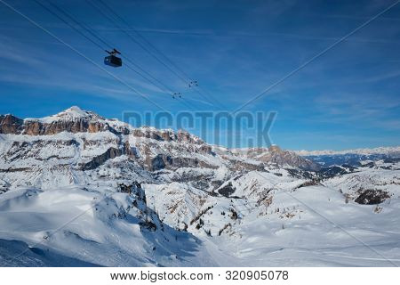 poster of View of a ski resort piste with people skiing in Dolomites in Italy with cable car ski lift. Ski are
