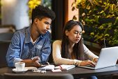 Hardworking Mixed Race Couple Of Students Experiencing Difficulties With Homework, Studying At Cafe, poster
