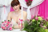 happy bride wearing white dress sits at table with candles and holds bouquet of roses