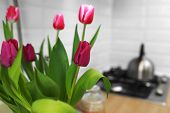 Tulips Bouquet Close Up At Home Standing On A Wooden Countertop In The Kitchen. Modern White U-shape poster