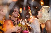 Multi-ethnic Group Of Adult Friends Wearing Halloween Costumes Drinking Cocktails While Enjoying Par poster