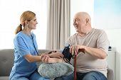 Nurse Measuring Blood Pressure Of Elderly Man Indoors. Assisting Senior People poster