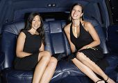 Two women in formal outfits in backseat of car