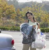 Woman carrying dry cleaning and bags of groceries to her car