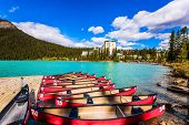 Beautiful red canoes for tourists are moored to the coast. The lake is surrounded by mountains and f poster